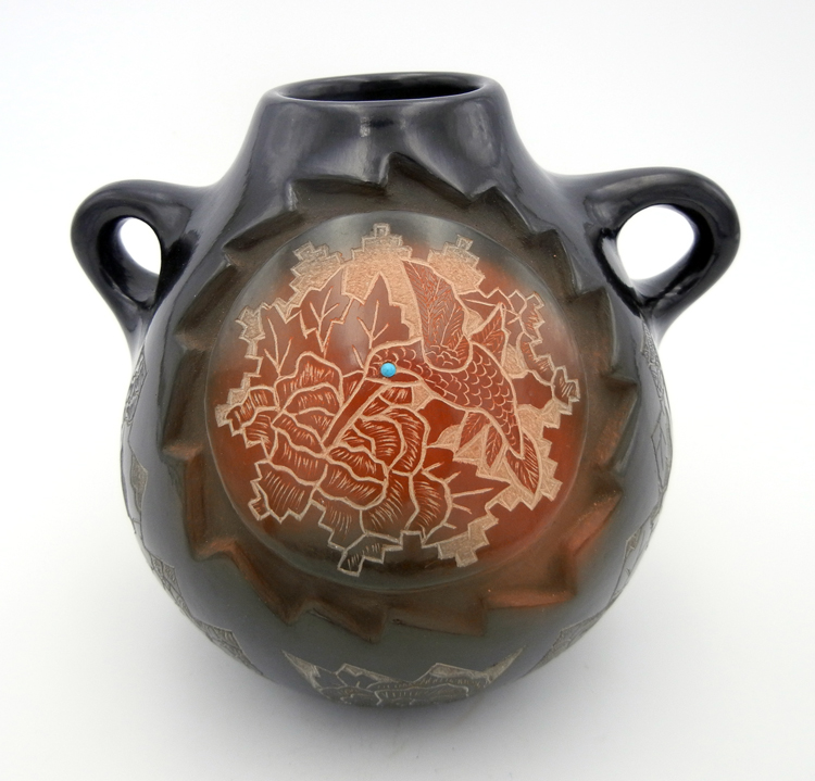 A black polished, etched canteen by Santa Clara potter Gwen Tafoya, featuring humminbirds, butterflies and flowers